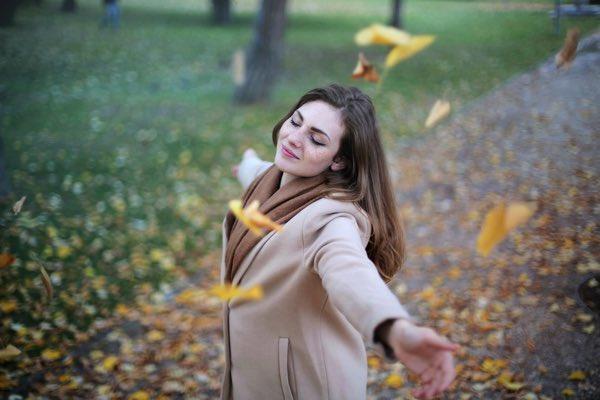 秋の落ち葉が舞い散る中、秋を感じる女性