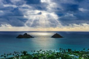 雲の合間から光が差し込む岩のある綺麗な海