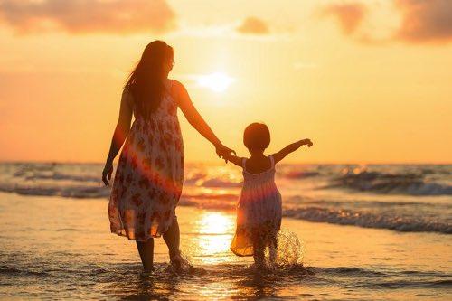 波打ち際で女の人と手を繋いでいる子ども