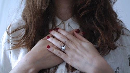 胸を手でおさえる女性