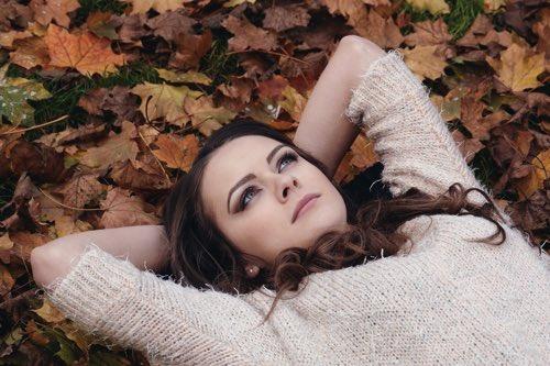 地面に横たわり考え事をしている女性