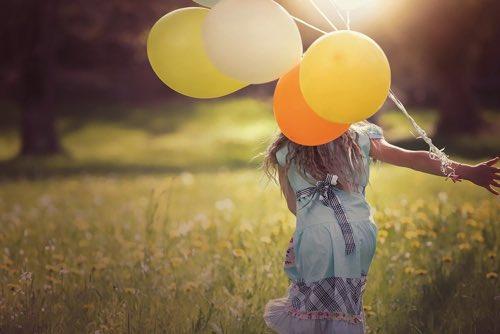 風船を持って草原を走る女の子