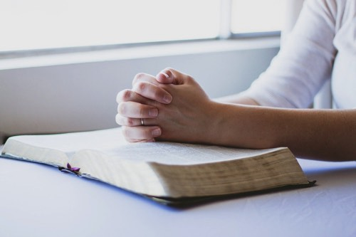 本の上に手を置いて祈る人